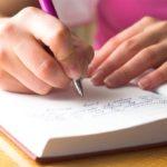 Frau führt ein schriftliches Haushaltsbuch