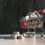 Kleiner Einkaufswagen mit Münzgeld drin, um das Geldsparen beim Lebensmitteleinkauf zu symbolisieren
